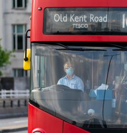 Driver of a double decker red London Bus driving with a face mask on