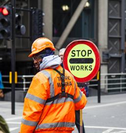 Traffic Marshall holding stop works sign